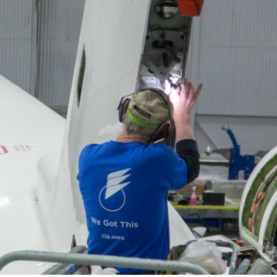 Interior regional aircraft conversion on Embraer aircraft - photo of technician working on the interior of an aircraft dorsal fin
