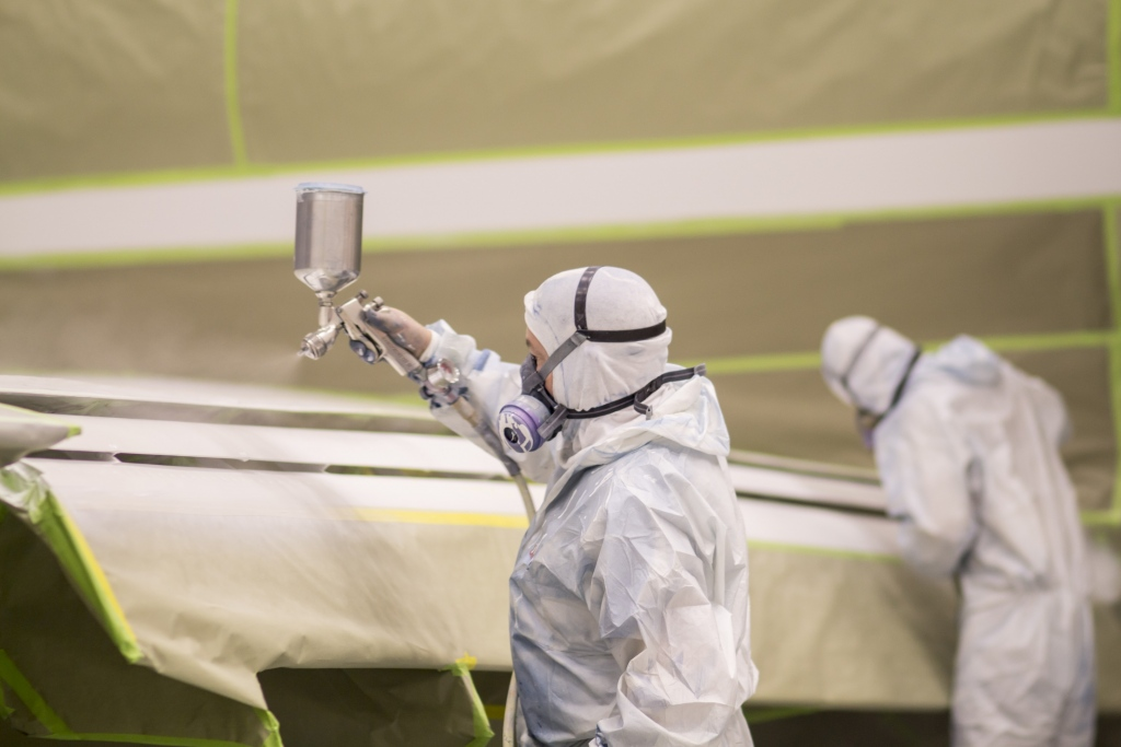 Interior regional aircraft conversion on Embraer aircraft - photo of two workers spray painting the wings of an aircraft