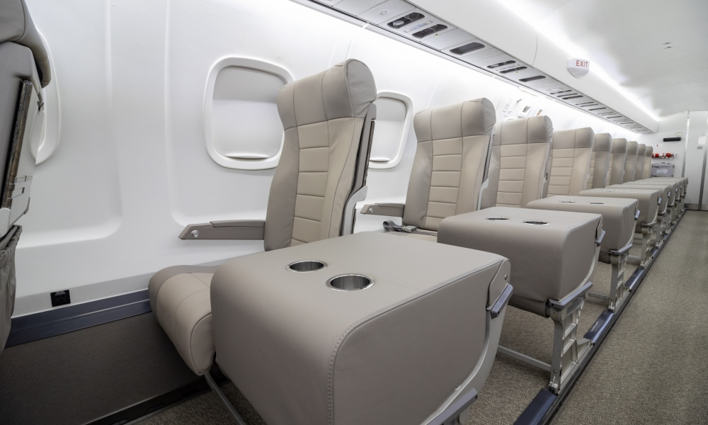 Interior regional aircraft conversion on Embraer aircraft - photo of aircraft aisle with gray seats and trays with two cup holders