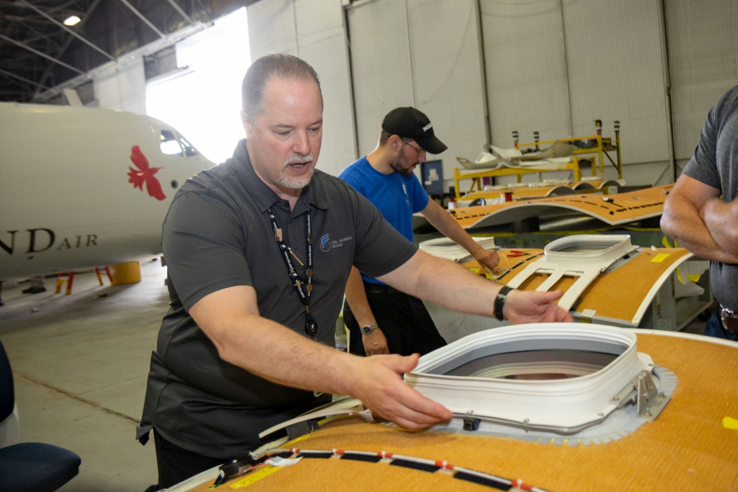 Interior regional aircraft conversion on Embraer aircraft - photo of workers assembling ceiling parts of an aircraft