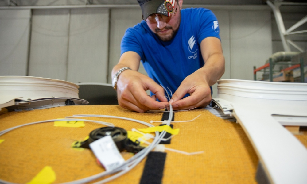 Interior regional aircraft conversion on Embraer aircraft - photo of technician installing bongiovi audio system onto top of plane