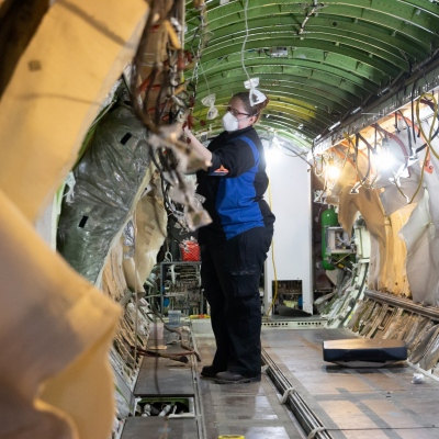 Interior regional aircraft conversion on Embraer aircraft - photo of worker with facemask working on the interior of an aircraft