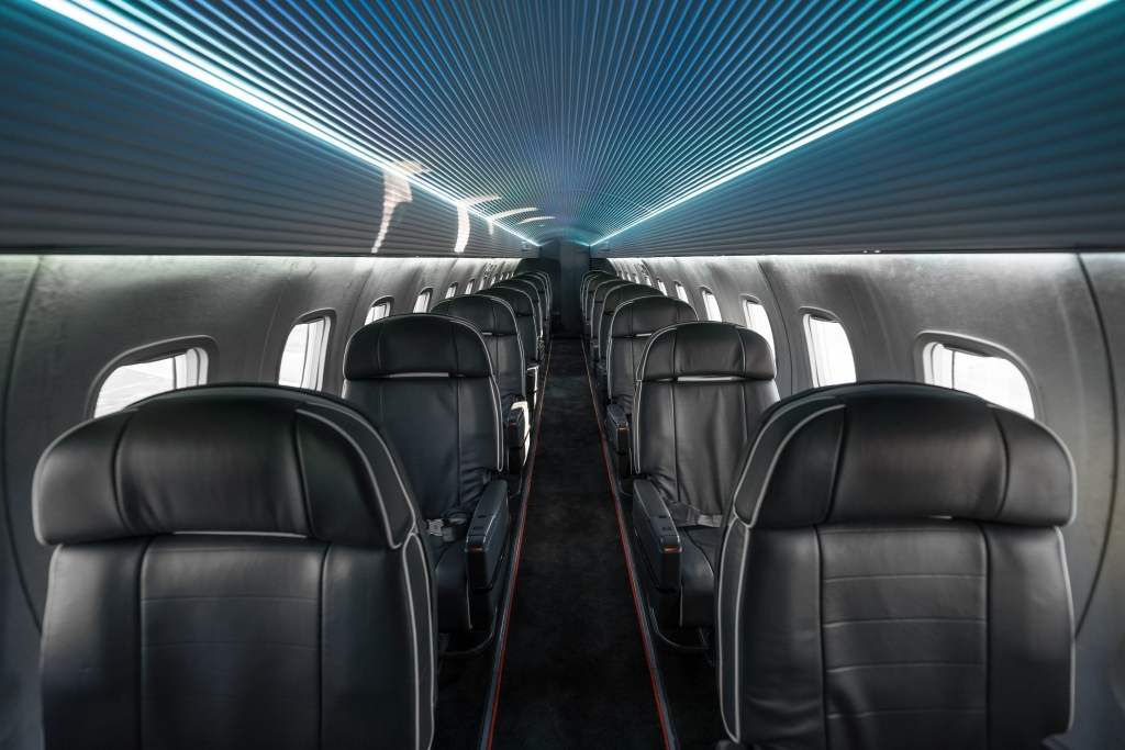 Interior regional aircraft conversion on Embraer aircraft - photo of brightly lit aircraft aisle with one seat on either side
