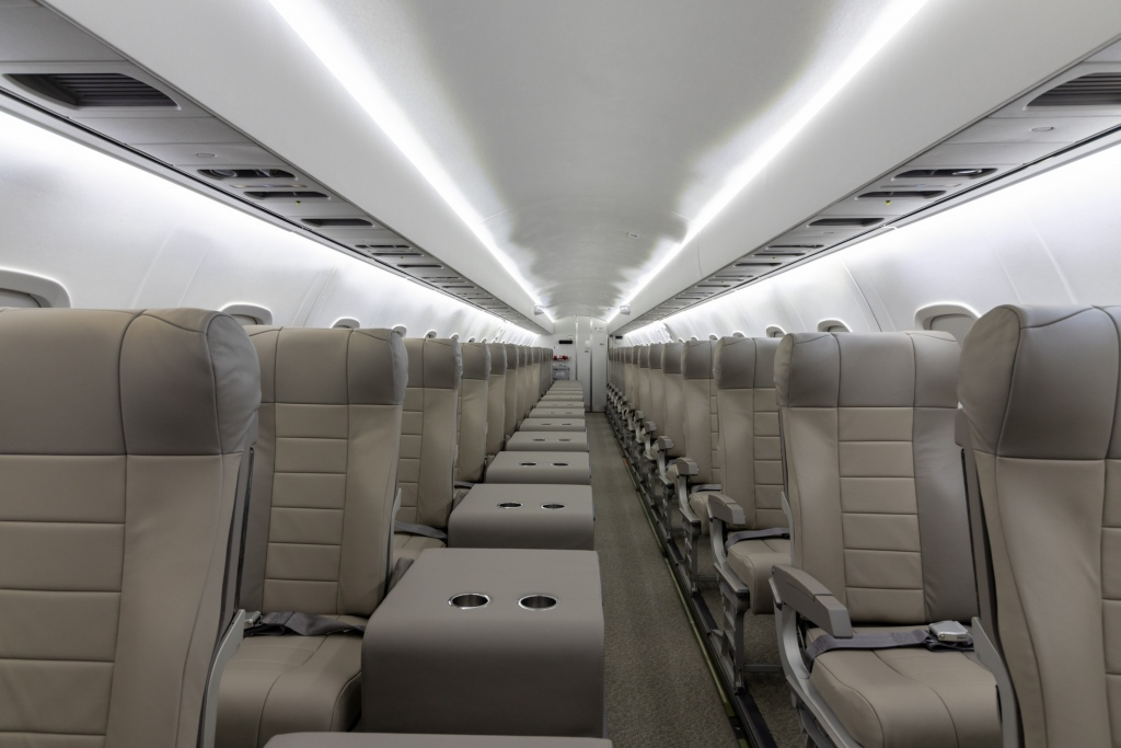 Interior regional aircraft conversion on Embraer aircraft - photo of aircraft aisle with one seat on either side and a tray with two cup holders next to the left seats