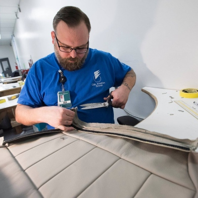 Interior regional aircraft conversion on Embraer aircraft - photo of a worker with a pair of scissors working on a fabric cover