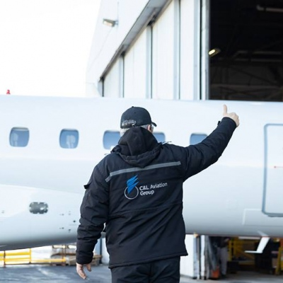 Interior regional aircraft conversion on Embraer aircraft - photo of man in c&l aviation jacket holding a thumbs up in front of a plane