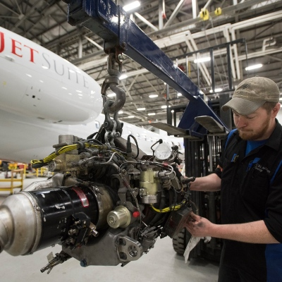 Interior regional aircraft conversion on Embraer aircraft - photo of a technician working on an aircraft engine