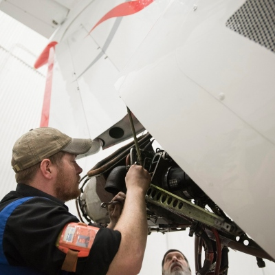 Interior regional aircraft conversion on Embraer aircraft - photo of two technicians working on the rear engine of an aircraft