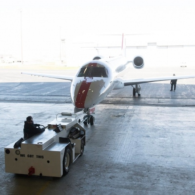 Interior regional aircraft conversion on Embraer aircraft - photo of a worker using equipment to pull an aircraft into a hanger