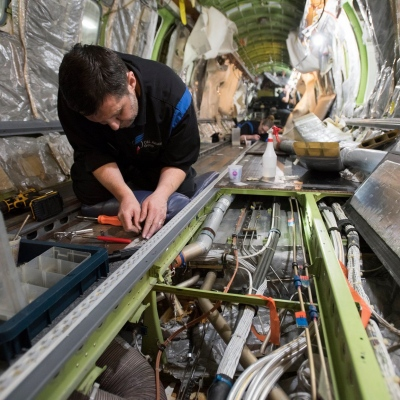 Interior regional aircraft conversion on Embraer aircraft - photo of a technician working on the wiring in the floor of an aircraft