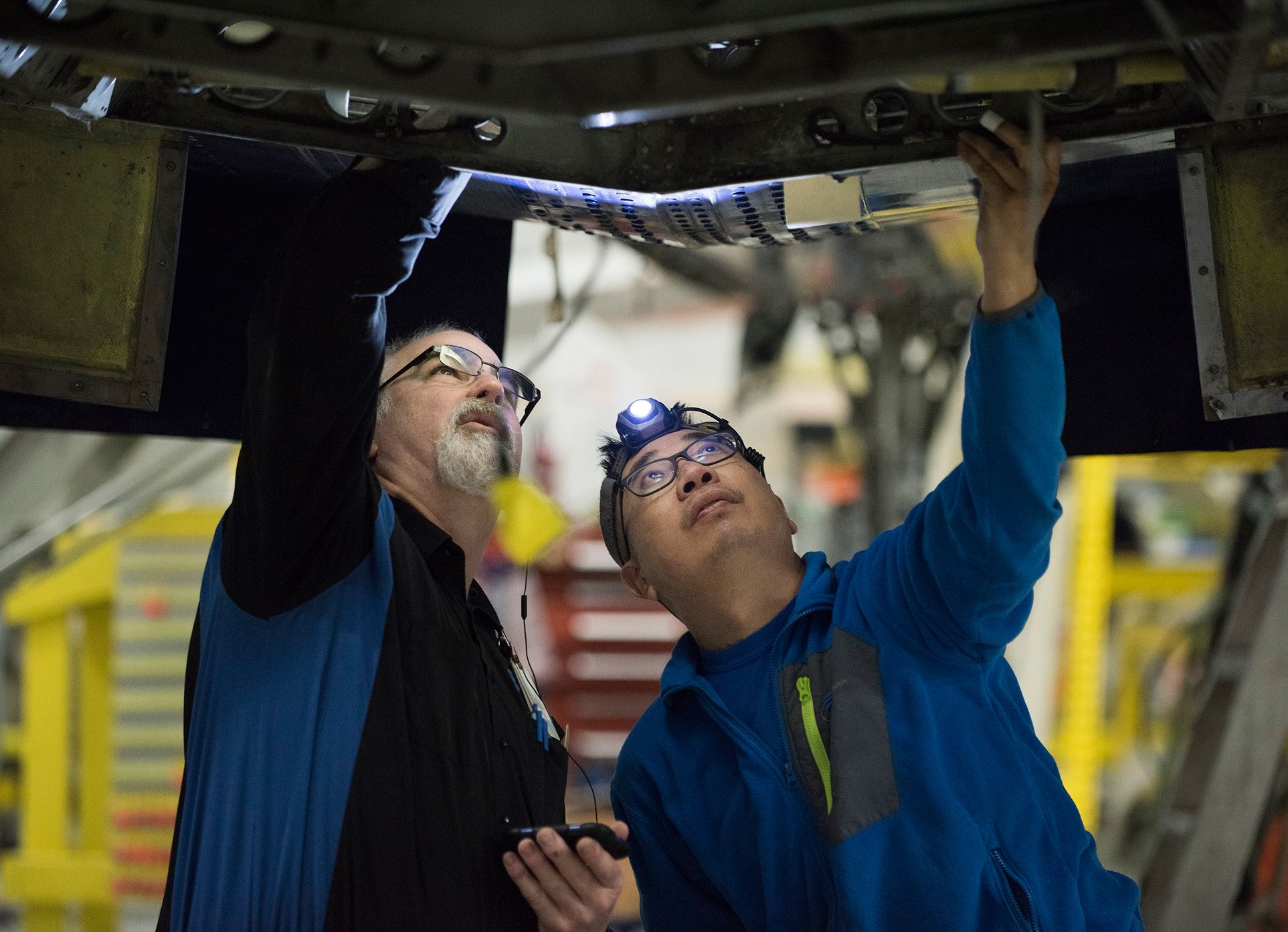 Interior regional aircraft conversion on Embraer aircraft - photo of two technicians looking in a panel on the underside of an aircraft