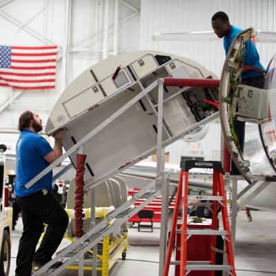 Interior regional aircraft conversion on Embraer aircraft - photo of two technicians carring equipment into an aircraft